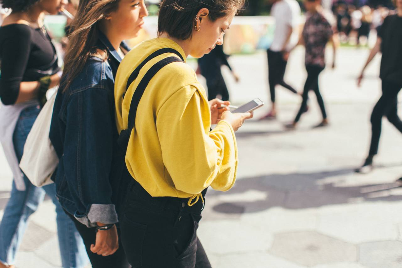 Tjej i gul hoodie kollar i sin mobil på Way out West.