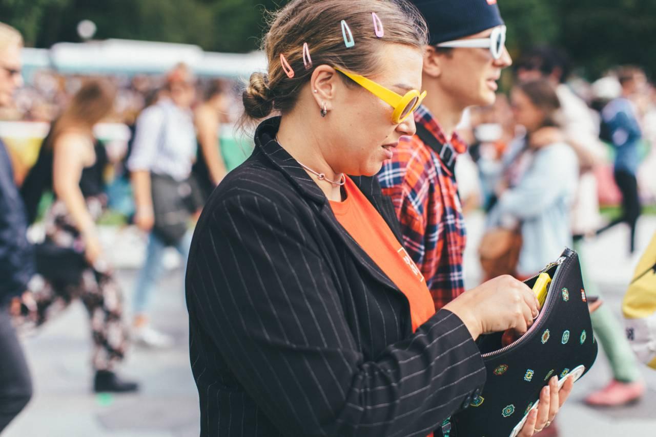Festivalgäst med färgglada hårspännen och gula solglasögon.