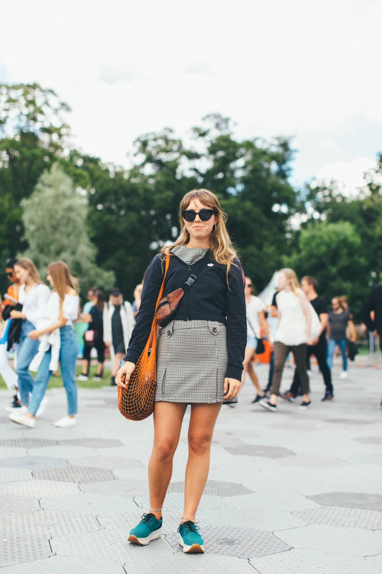 Festivaloutfit på gäst, klädd i rutig miniklänning, adidaströja, sneakers och orange nätväska..