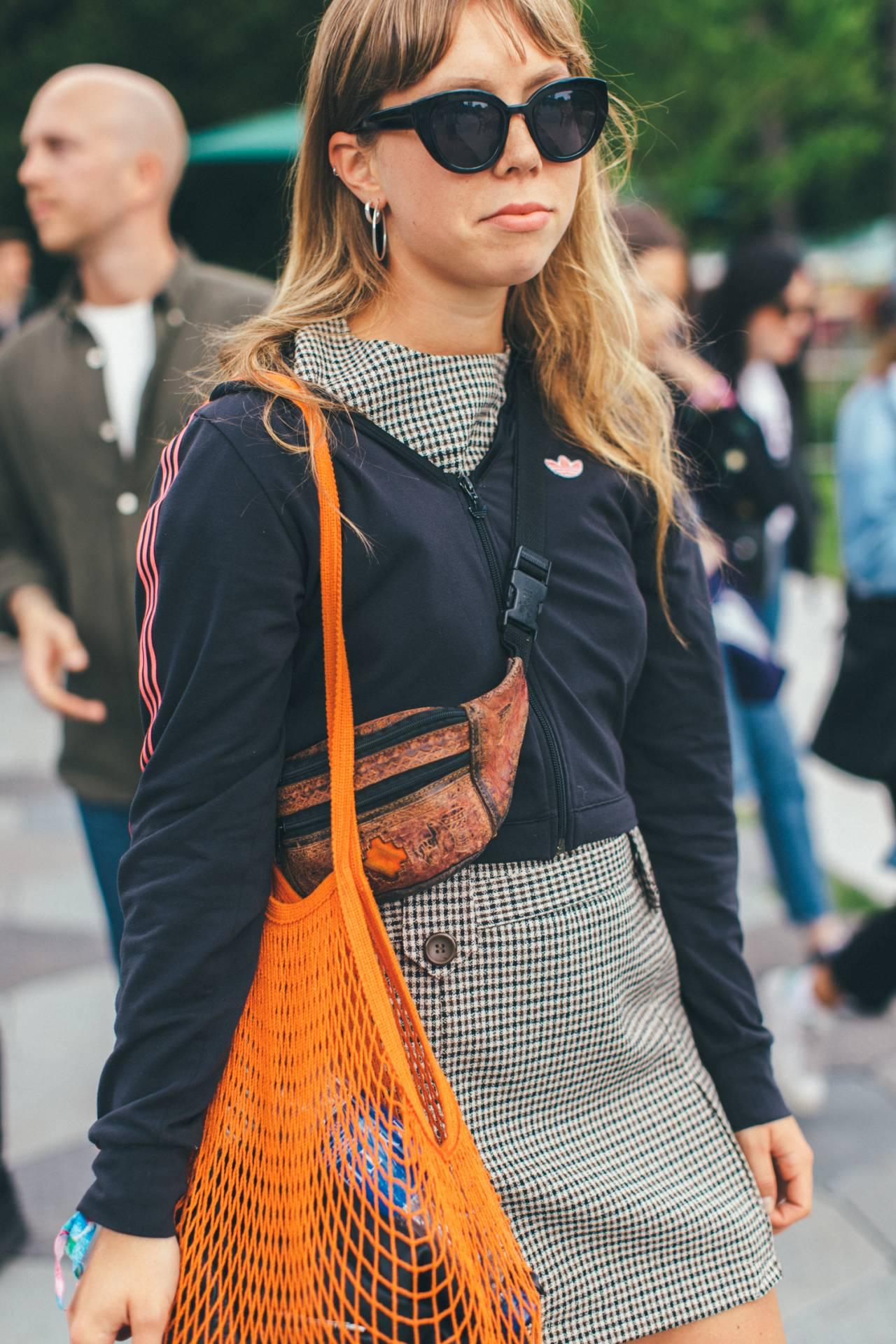 Tjej i rutig miniklänning, adidaströja och orange nätväska.