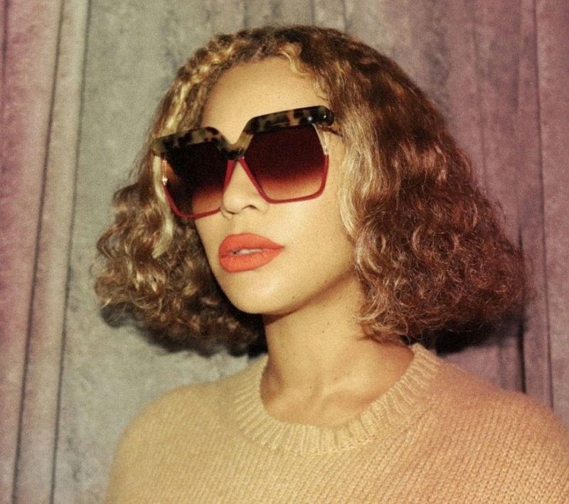 Beyoncé i den perfekta pagen, stora solisar och beige stickad tröja.