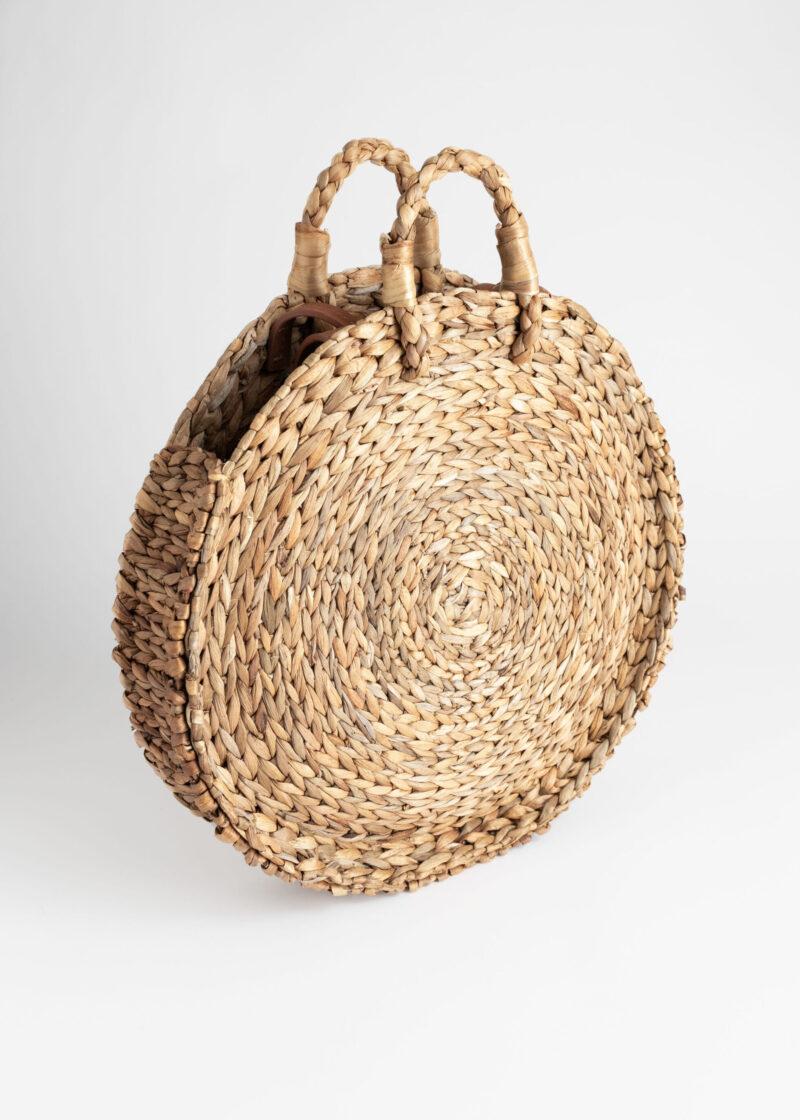Rund stråväska med korta handtag och ett längre remband i läder från & Other stories. Här kan du shoppa stråväskan!