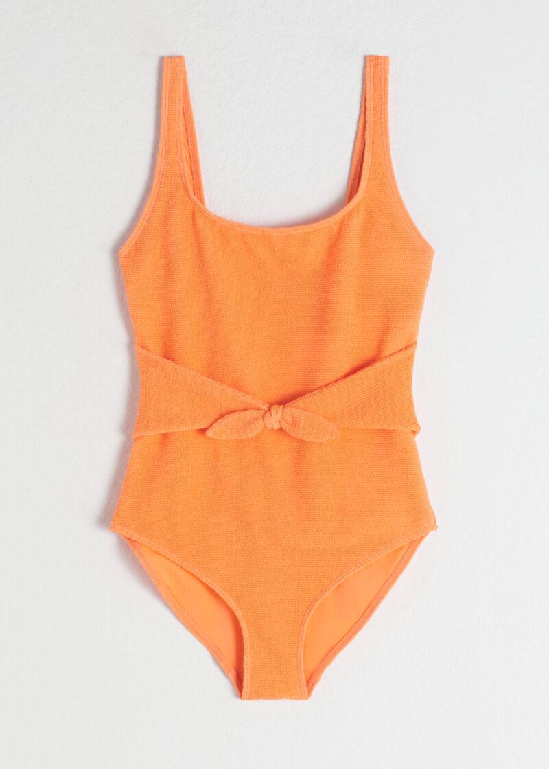 Orange baddräkt i ribbat material med djup rygg och söt knytdetalj i midjan. Från & Other stories. Shoppa baddräkten här!