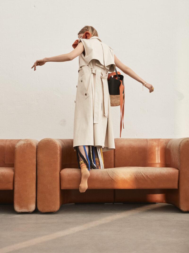 Modell står på rostbrun soffa i ljusbeige kappa från Bottega Veneta.