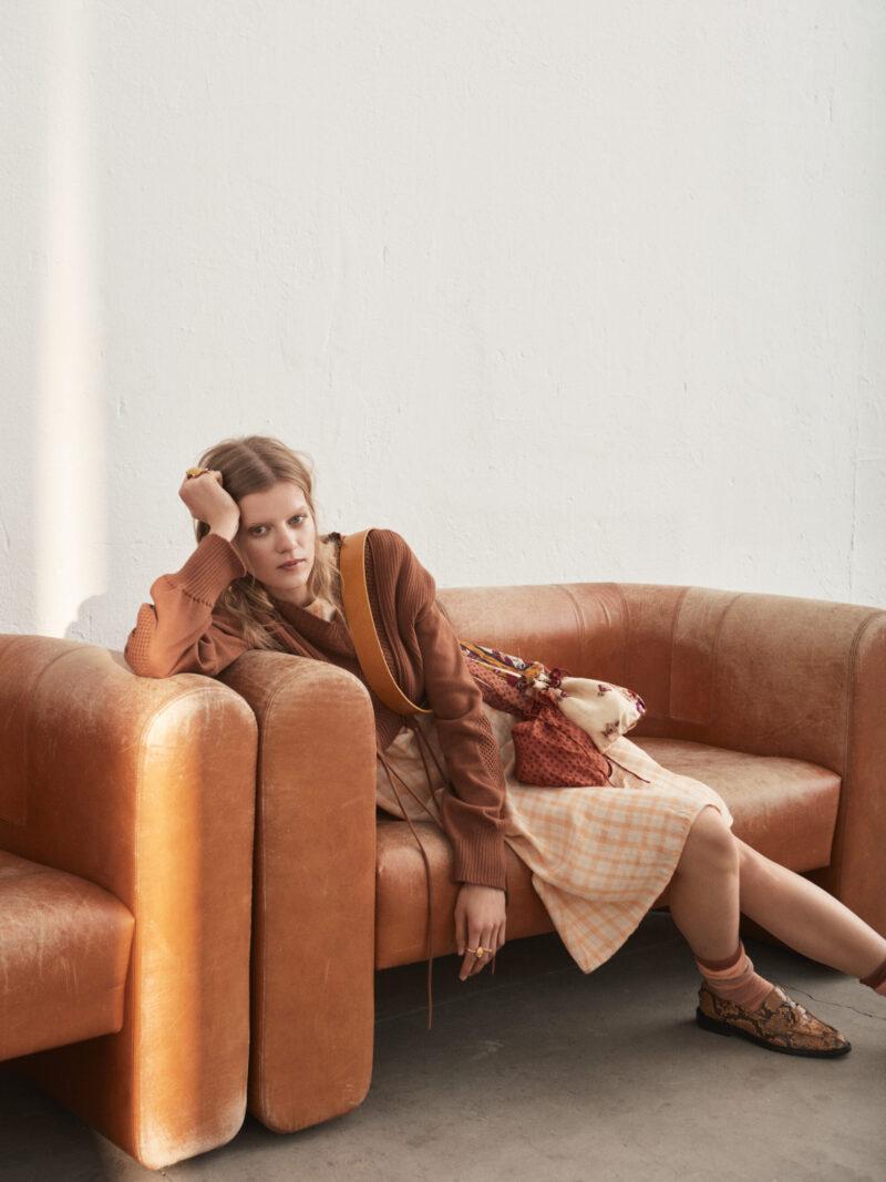 Modell halvsittandes i rostbrun soffa, iklädd klänning från Acne Studios.