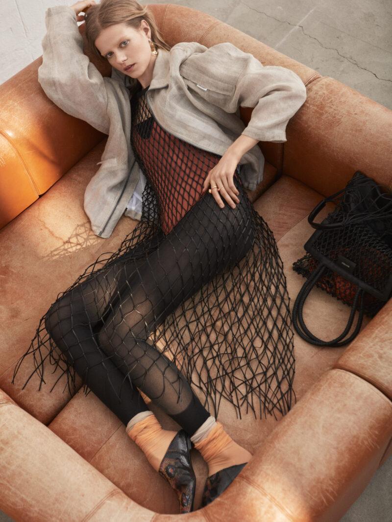 Modell liggandes i soffa, iklädd beige jacka från Our Legacy och klänning från Christian Dior
