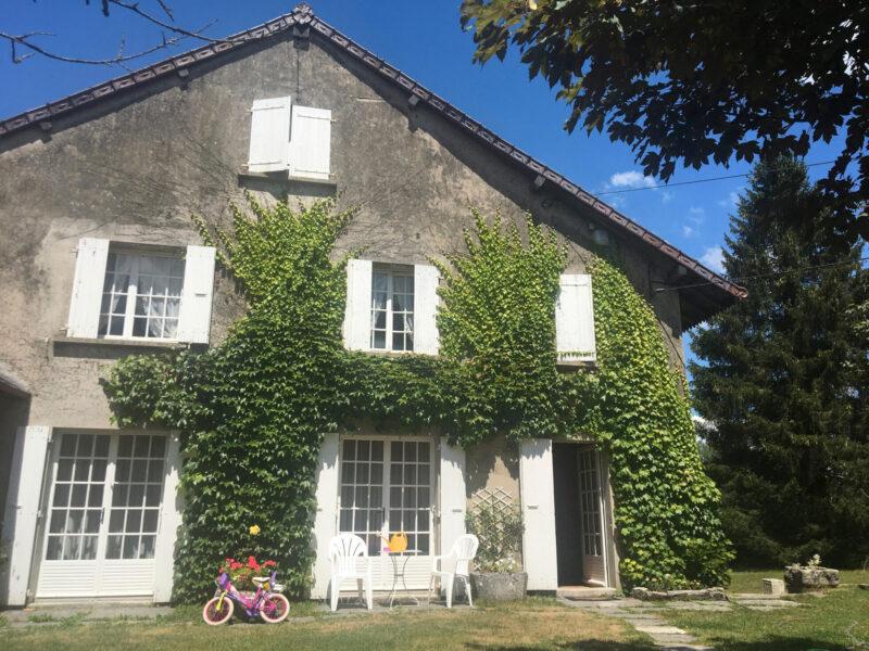 Grått hus med murgröna i franska Jura
