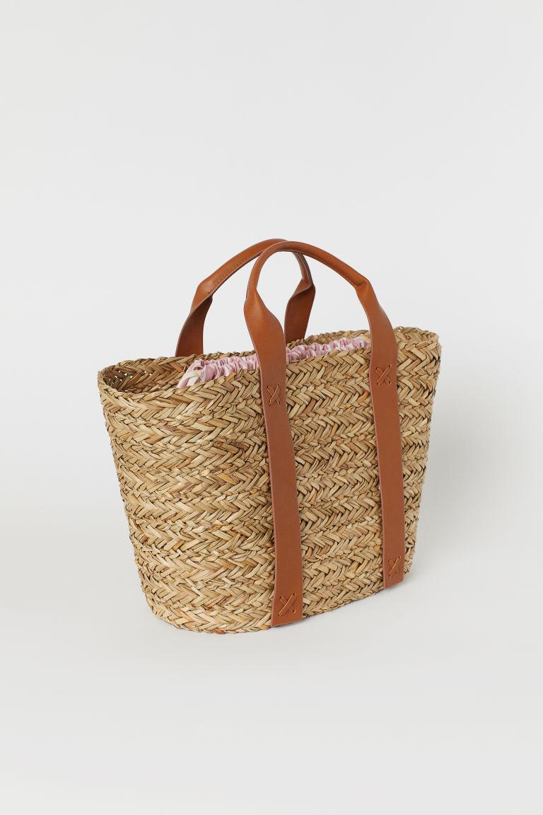 Mindre stråväska med dubbla remmar i brun läderimitation och rosa fastsydd påse