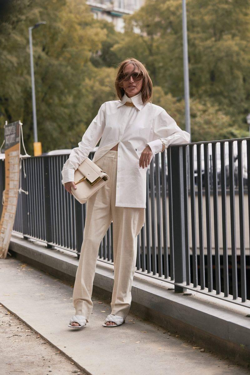 Milano Fashion Week Streetstyle SS20. Kvinna i vit skjorta och beigea byxor.