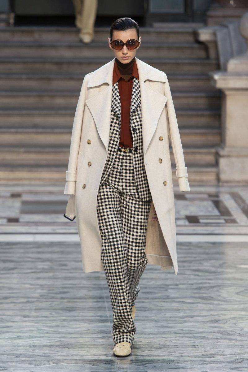 Victoria Beckham på London Fashion Week SS20, vit trenchcoat