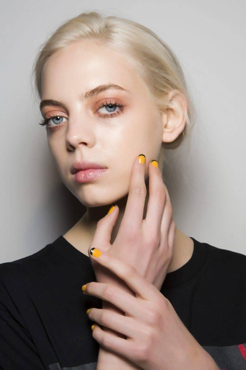 Modell med gula naglar.