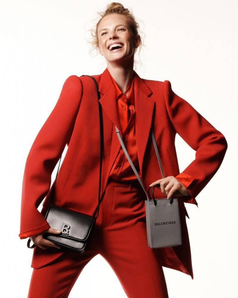 Röd kostym, skjorta och svarta väskor från Balenciaga
