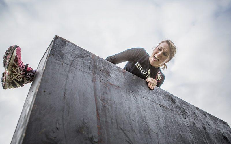 Kvinna klättrar över hinderbanevägg