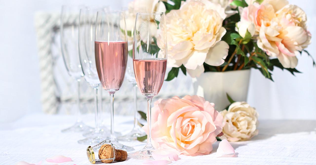 glas med rosa bubbel och blommor runt omkring