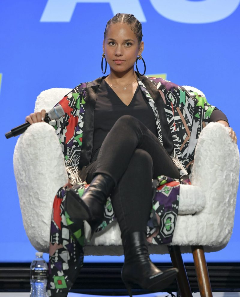 Alicia Keys sitter I en vit fåtölj