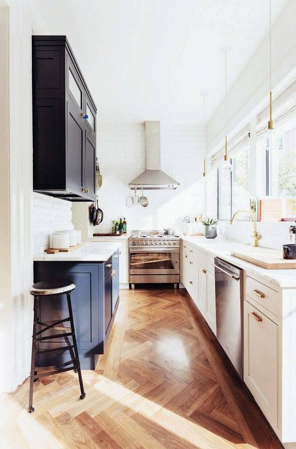 Avlångt kök med vita luckor vid fönstret och mörka mot väggen.