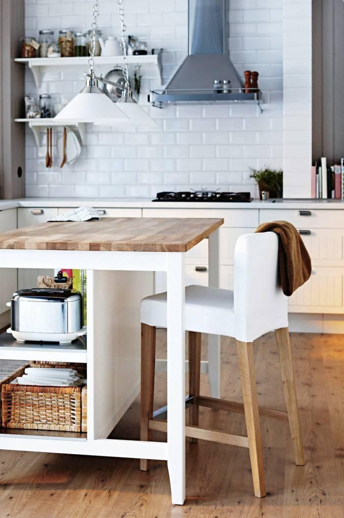 Kök med ekgolv och bord med förvaring.