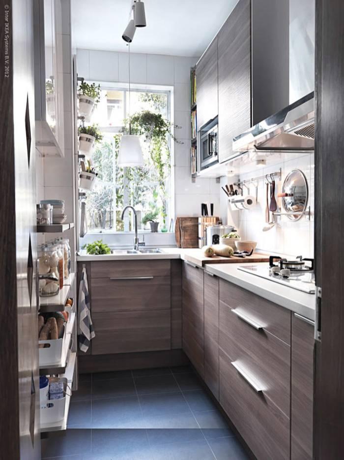 Litet kök med träluckor och stort fönster.